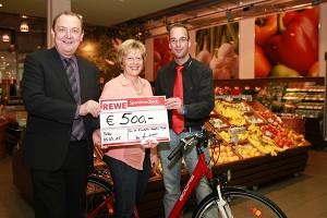 Wir sind zu Gast im REWE-Markt. Frau Pfeffermann sitzt auf einem E-Bike und hält stolz einen Scheck über 500,00 € in ihren Händen. Herr Erb und Herr Grasmück stehen rechts und links neben ihr.