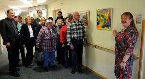 Auf der großen Diele sind im Hospiz neue Bilder zu sehen. Frau Siemens steht rechts von einem sehr farbenfrohen Bild und weist mit ihrer Hand darauf. Links neben diesem Bild steht ein Gruppe von Menschen, welche der Erklärung von Frau Siemens lauschen.