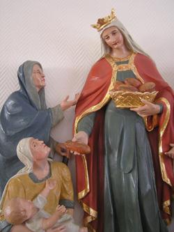 Eine Statur der Heiligen Elisabeth zeigt sie beim Austeilen von Brot. In der linken Hand hält sie einen Brotkorb. Ihre Linke reicht einem Bedürftigen ein Stück davon. Vor den Beschenkten hockt eine ebenfalls bedürftige Frau mit einem Kind auf dem Schoß. Mutter und Kind strecken ihre Arme Elisabeth entgegen.