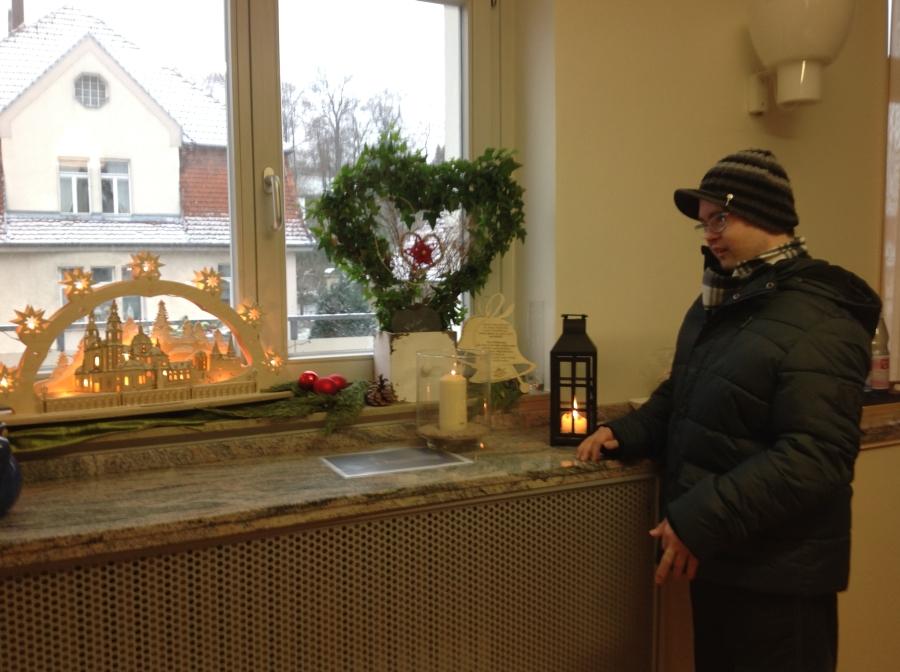 Florian steht rechts neben einem Schwibbogen. Vor diesen leuchtenden Bogen hat er das brennende Friedenslicht gestellt.  Foto: Hospiz St. Elisabeth